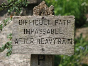 "sign post along the path reads ""difficult path - impassable after heavy rain"""