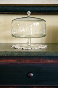 glass pedestal cake saver with dome and doily